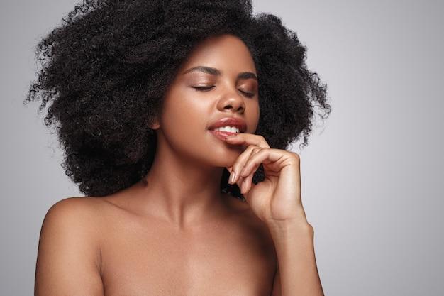Alegre modelo negro tocando el labio