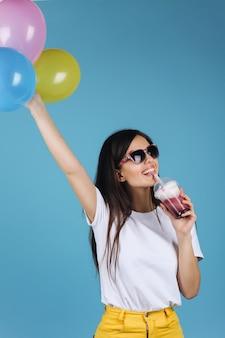 Alegre morena en gafas de sol negras se ve feliz posando con un cóctel y globos