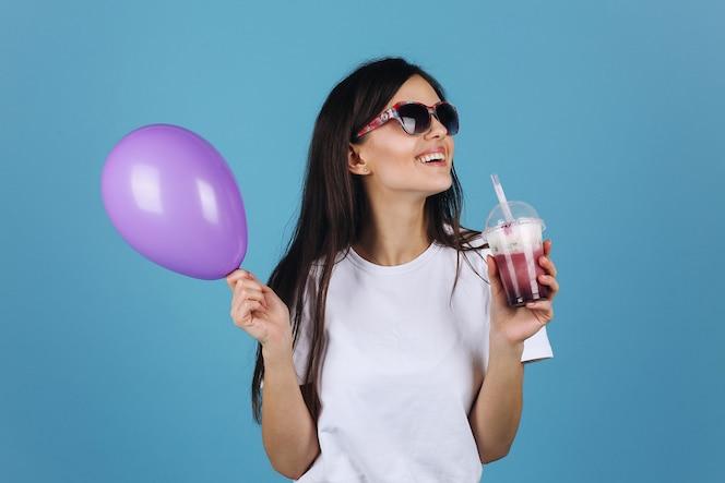 Alegre morena en gafas de sol negros se ve feliz posando con un cóctel y un globo