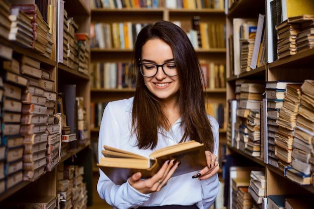 Alegre morena estudiante leyendo el libro en la biblioteca, de pie entre los pasillos de los estantes de diferentes libros antiguos