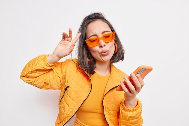 Alegre morena mujer asiática baila al ritmo de la canción favorita y se mueve al ritmo de la música sostiene el teléfono inteligente moderno lleva gafas de sol naranjas de moda, chaqueta elegante expresa felicidad y modelos de alegría interior