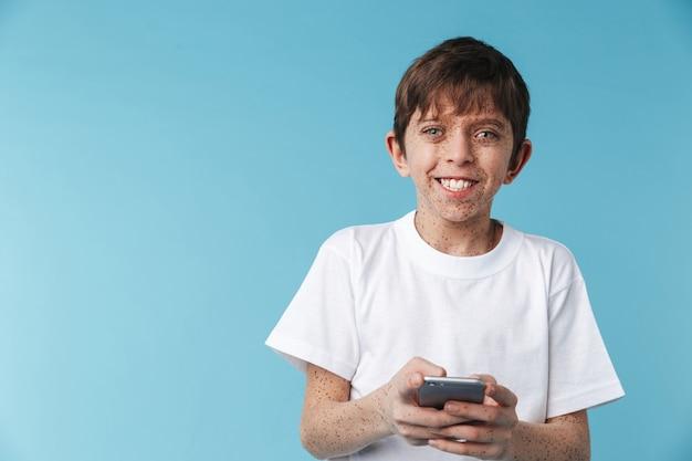 De alegre muchacho caucásico con pecas vistiendo camiseta blanca casual sonriendo y sosteniendo smartphone aislado sobre pared azul
