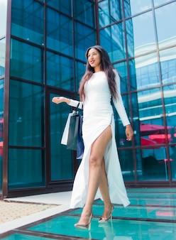 Alegre mujer afro en vestido blanco hermoso sosteniendo muchas bolsas de papel mientras caminaba frente al edificio de negocios con ventanas azules. concepto de adicto a las compras.