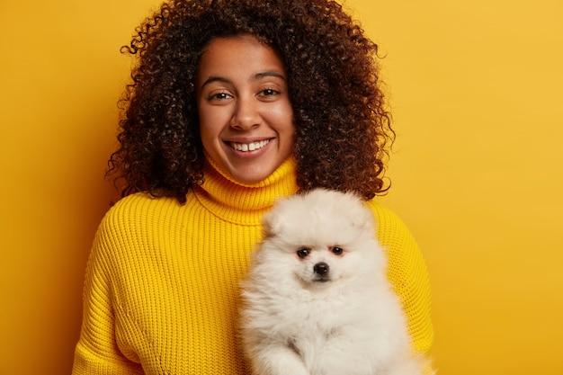 Alegre mujer afroamericana con una gran sonrisa, sostiene un perro de pomerania blanco, trabaja como voluntaria, encuentra refugio para los animales, viste un suéter amarillo.