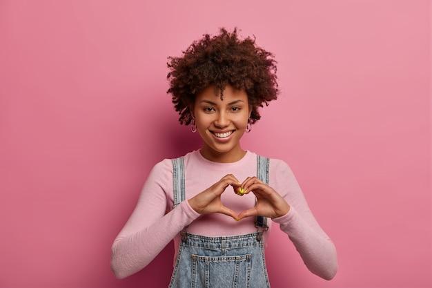 Alegre mujer afroamericana hace un gesto de corazón con las manos, se confiesa enamorado, sonríe positivamente, viste un atuendo informal, posa contra la pared rosa pastel. sentimiento romántico, concepto de lenguaje corporal
