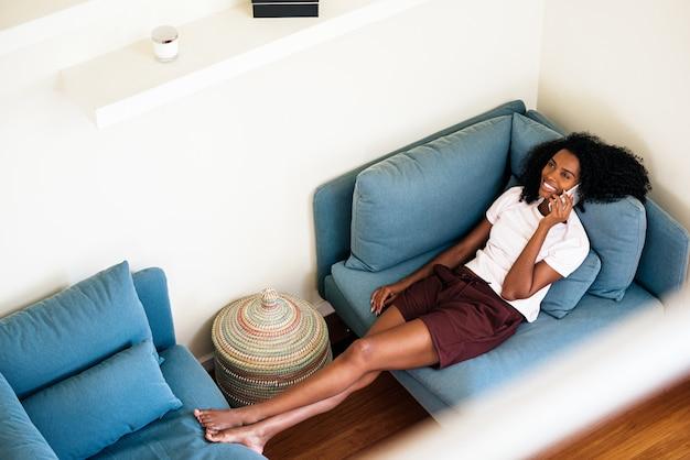 Alegre mujer afroamericana llamando por teléfono inteligente mientras descansa en casa