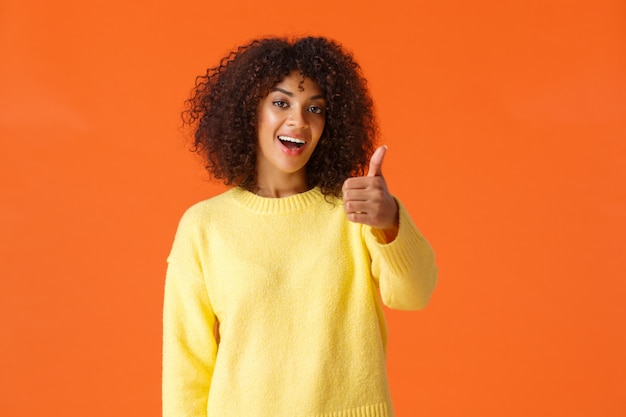 Alegre mujer afroamericana moderna saliente con el pelo rizado, mostrando el pulgar hacia arriba como, aprobación o gesto de alegría, diciendo todo bien, sí, sonriendo complacido, pared naranja
