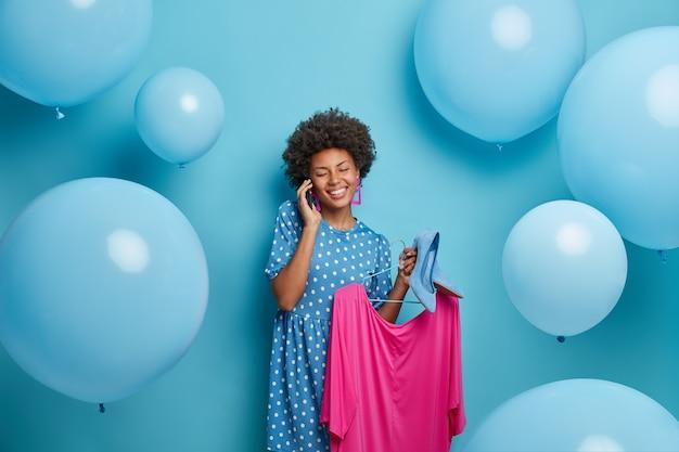 Alegre mujer afroamericana se prepara para charlas de fiesta con un amigo a través de un teléfono inteligente elige el atuendo para usar sostiene el vestido en perchas y zapatos de tacón alto