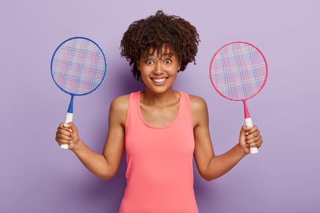 Alegre mujer afroamericana sostiene dos raquetas de tenis, invita a unirse a ella y jugar, descansa entre partidos de tenis