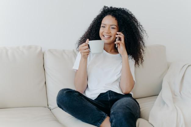 La alegre mujer afroamericana tiene un descanso para tomar café en la sala de estar, se sienta en el sofá y llama a un amigo a través de un dispositivo moderno
