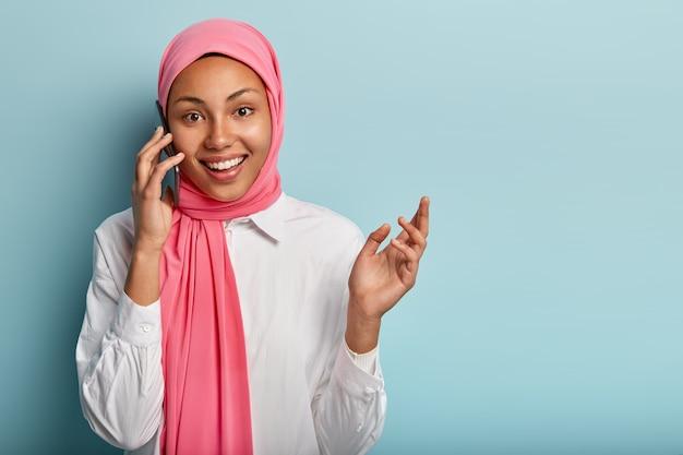 Alegre mujer árabe tiene conversación telefónica, gestos con las manos, explica algo activamente