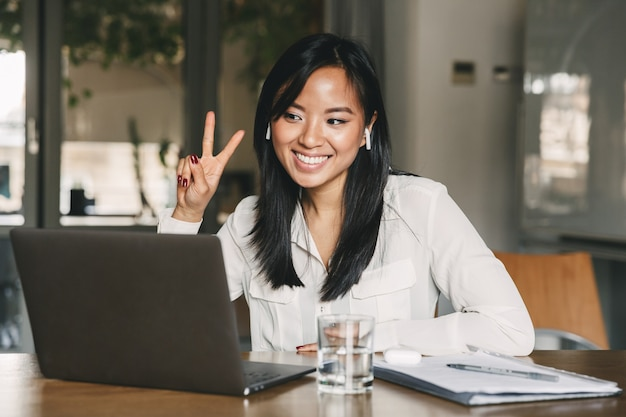 Alegre mujer asiática de 20 años con camisa blanca y auricular sonriendo y mostrando el signo de la victoria, mientras mira la pantalla de la computadora portátil en la oficina