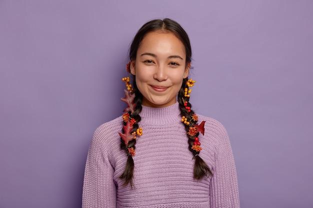 Alegre mujer asiática natural celebra el otoño, tiene dos trenzas decoradas con hojas rojas de otoño, bayas y flores, viste un suéter morado, aislado en la pared violeta. tiempo de octubre
