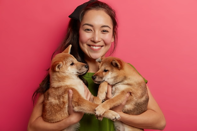Alegre mujer asiática posa con dos cachorros pequeños, le gustan los perros shiba inu, sonríe ampliamente, recibe buenas noticias del veterinario, feliz de tener mascotas saludables.