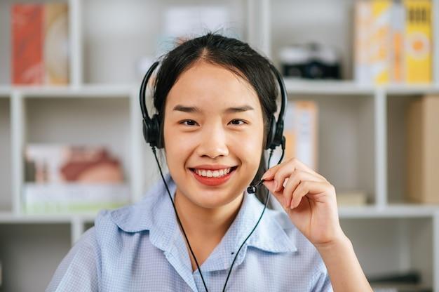 Alegre mujer asiática usa auriculares sonriendo y usa la conferencia de transmisión de videollamadas de la computadora portátil para trabajar en línea durante la cuarentena covid-19 autoaislamiento en casa, trabajar desde el concepto de hogar