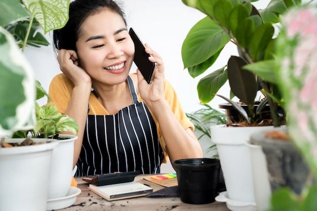 Alegre mujer asiática vendiendo plantas en línea hablando por un teléfono inteligente