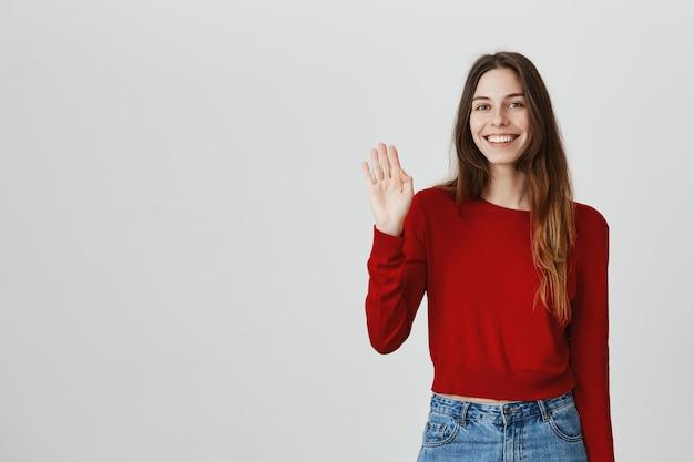 Alegre mujer atractiva amigable agitando la mano, saludando