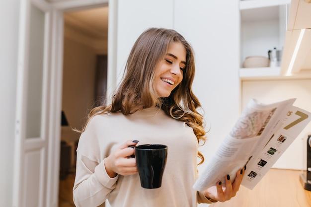 Alegre mujer blanca en traje beige leyendo noticias en la cocina mientras bebe café