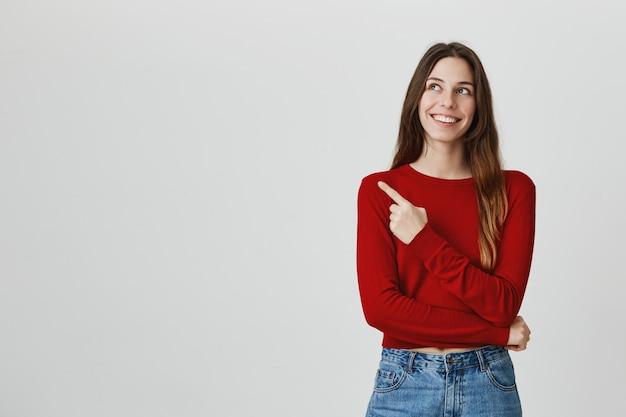 Alegre mujer bonita sonriente apuntando, mirando la esquina superior izquierda en el anuncio