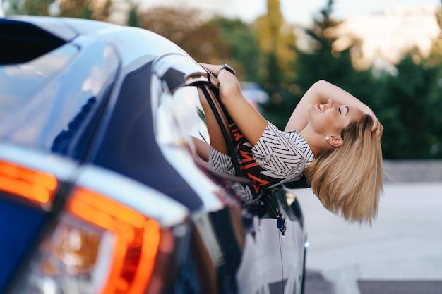 Alegre mujer caucásica conduce a través de la pintoresca ciudad soleada y agita los brazos mientras se extiende por la ventana del coche en un hermoso día