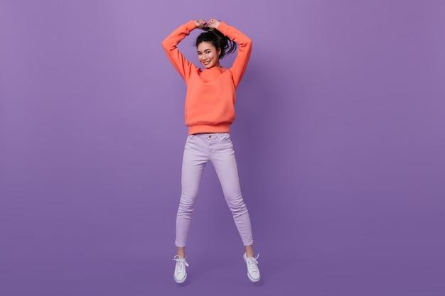 Alegre mujer coreana saltando sobre fondo morado. disparo de estudio de atractiva mujer asiática bailando con sonrisa.