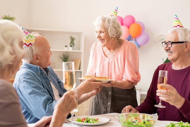 Alegre mujer de edad con pastel de cumpleaños mirando a uno de los amigos brindando con champán en la fiesta de casa