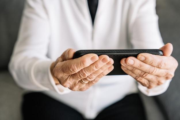Alegre mujer de edad sentada en el sofá en casa y hablando por video chat con la familia en el teléfono móvil