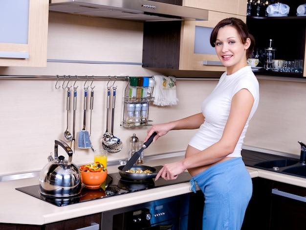 La alegre mujer embarazada se prepara para comer