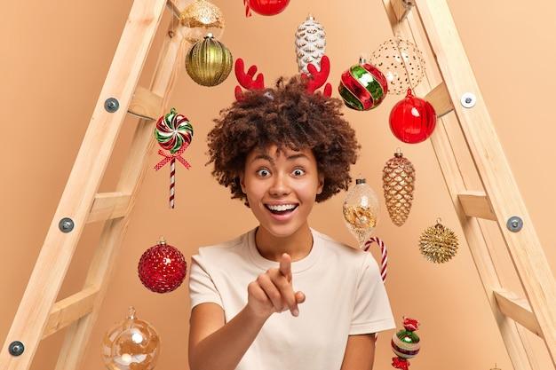 Alegre mujer étnica atractiva con cabello rizado indica directamente a la cámara que tiene una amplia sonrisa se prepara para la celebración navideña usa una escalera para colgar juguetes navideños ve algo increíble en el frente