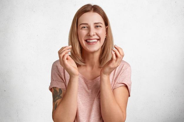 Alegre mujer europea con peinado ondulado, agarra las manos con felicidad, tiene una sonrisa con dientes, muestra una sonrisa blanca y brillante