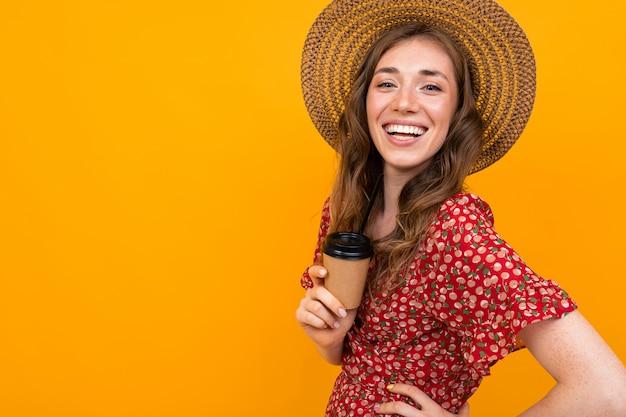 Alegre mujer europea se ríe sobre un fondo naranja, una niña con un sombrero y un vestido rojo con café en mano