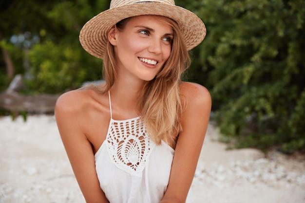 Alegre mujer feliz emocional con expresión satisfecha, viste ropa de verano, se ve feliz a un lado, está de buen humor después de pasear por la playa de arena, sueña con algo agradable. descanso de verano