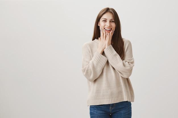 Alegre mujer feliz reacciona a noticias asombrosas o sorpresa, luciendo halagada