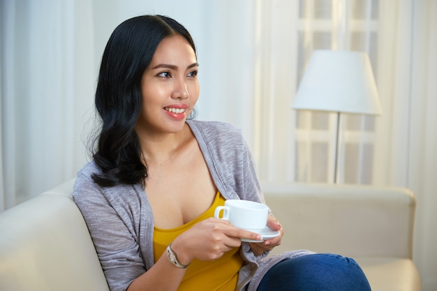 Alegre mujer filipina con bebida caliente en el sofá