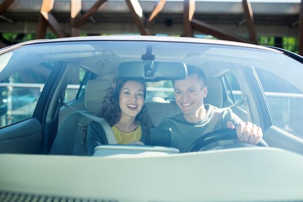 Alegre mujer y hombre sentado en un automóvil de pasajeros