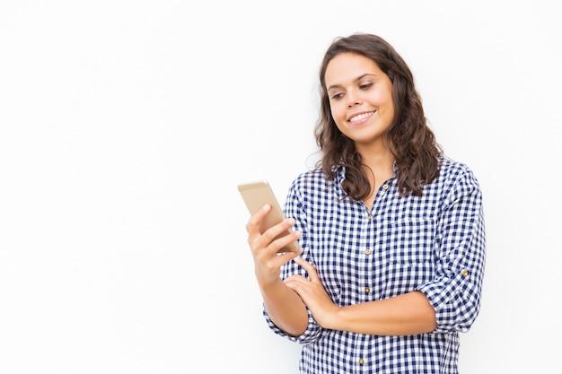 Alegre mujer latina positiva con mensaje de lectura de teléfono inteligente