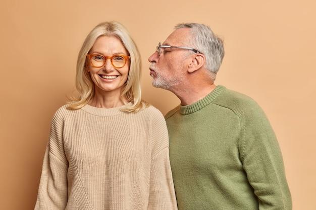 Alegre mujer de mediana edad europea sonríe suavemente mientras recibe un beso del marido, tienen buenas relaciones, se aman durante mucho tiempo aislados sobre una pared marrón