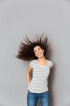 Alegre mujer morena en casual posando con sincera sonrisa sacudiendo su cabello mientras está de buen humor sobre la pared gris