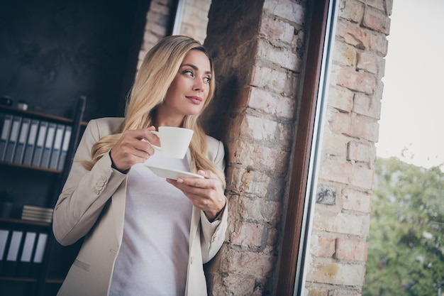 Alegre mujer de negocios mirando lejos de la ventana para relajar los ojos mientras se calienta con una bebida caliente en la taza