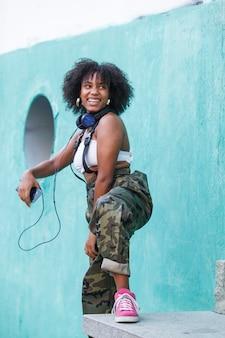 Alegre mujer negra con actitud positiva usando tecnología