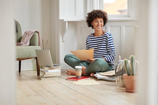 Alegre mujer negra se siente complacida, posa en posición de loto, lee el informe financiero