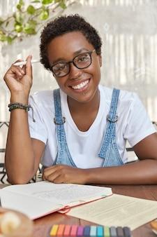Alegre mujer negra toma pocas notas en el diario, está de buen humor, sostiene un bolígrafo en la mano, lee información de los papeles
