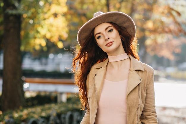 Alegre mujer pelirroja de pelo largo con elegante sombrero pasar tiempo libre, explorando la ciudad en día de otoño