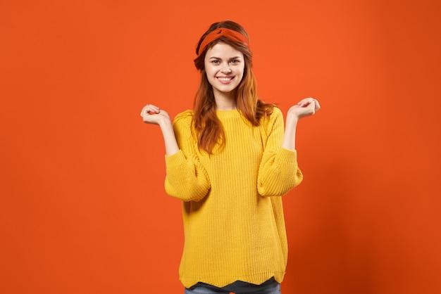 Alegre mujer pelirroja en suéter amarillo emociones streetwear moda fondo rojo.