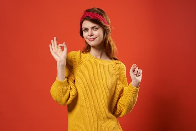 Alegre mujer pelirroja en suéter amarillo emociones streetwear moda fondo rojo