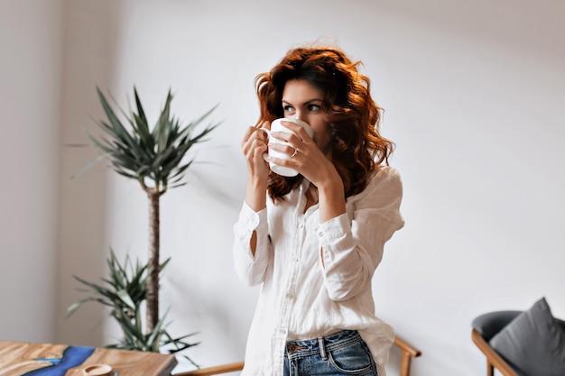 Alegre mujer pelirroja tomando café disfrutando del ocio en la cafetería y mirando la ventana durante el descanso