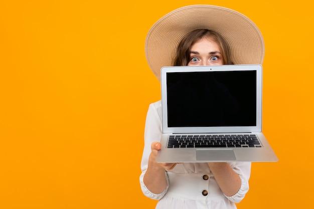 Alegre mujer de pelo castaño con un sombrero sostiene una computadora portátil a la altura del pecho con la pantalla hacia adelante, retrato sobre una naranja