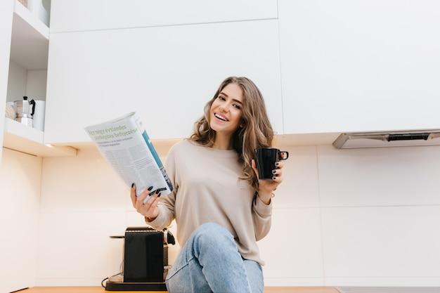 Alegre mujer de pelo largo con expresión de cara feliz leyendo noticias en la mañana