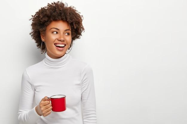 Alegre mujer de piel oscura complacida bebe té de una taza roja, mira en el lado derecho, feliz de tener tiempo libre