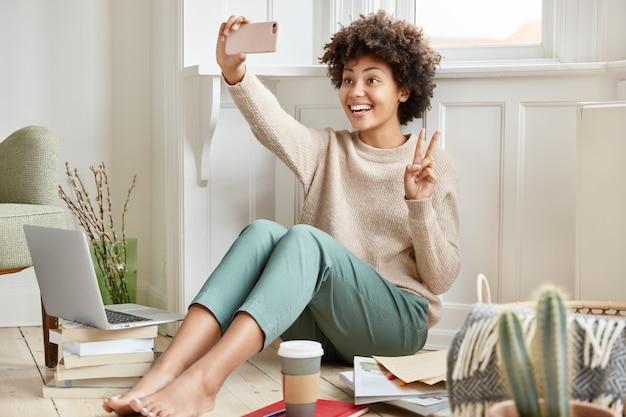 Alegre mujer de piel oscura hace videollamada con teléfono celular, muestra el signo de la paz